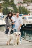 Ευτυχής οικογένεια με τα σκυλιά στην αποβάθρα το καλοκαίρι Στοκ φωτογραφία με δικαίωμα ελεύθερης χρήσης