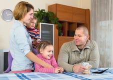 Ευτυχής οικογένεια με τα τραπεζογραμμάτια Στοκ Εικόνες