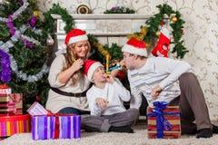 Ευτυχής οικογένεια με τα δώρα Χριστουγέννων. Στοκ Φωτογραφία