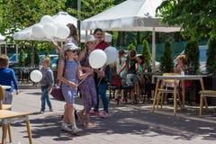 Ευτυχής οικογένεια με τα baloons στην οδό κατά τη διάρκεια της ημέρας προστασίας παιδιών Στοκ Εικόνες