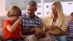 Ευτυχής οικογένεια με τη γάτα κατοικίδιων ζώων απόθεμα βίντεο