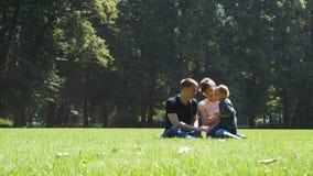 Ευτυχής οικογένεια με τη συνεδρίαση μωρών στη χλόη στο θερινό πάρκο απόθεμα βίντεο