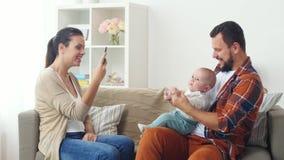 Ευτυχής οικογένεια με τη φωτογράφιση μωρών στο σπίτι απόθεμα βίντεο
