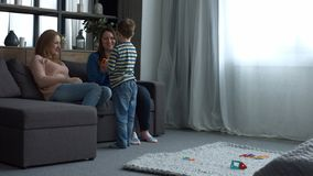 Ευτυχής οικογένεια με τη χαλάρωση παιδιών στο εσωτερικό δωμάτιο απόθεμα βίντεο