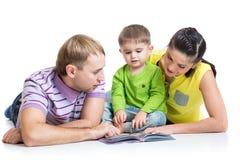 Ευτυχής οικογένεια με το βιβλίο παιδιών ανάγνωσης γιων Στοκ Εικόνα
