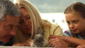Ευτυχής οικογένεια με το κουνέλι κατοικίδιων ζώων απόθεμα βίντεο