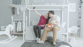 Ευτυχής οικογένεια με το μωρό που παίρνει το κοινό selfie στο σπίτι φιλμ μικρού μήκους
