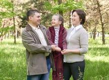 Ευτυχής οικογένεια με το παιδί στο θερινό πάρκο, το φως του ήλιου, την πράσινα χλόη και τα δέντρα Στοκ Φωτογραφίες