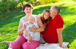 Ευτυχής οικογένεια με δύο παιδιά που κάθονται στη χλόη Στοκ Εικόνες