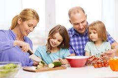Ευτυχής οικογένεια με δύο παιδιά που κάνουν το γεύμα στο σπίτι Στοκ Φωτογραφίες