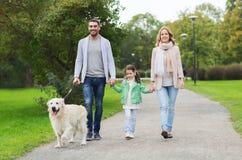 Ευτυχής οικογένεια με retriever του Λαμπραντόρ το σκυλί στο πάρκο Στοκ εικόνα με δικαίωμα ελεύθερης χρήσης