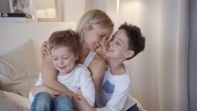 Ευτυχής οικογένεια - μητέρα με δύο γιους που αγκαλιάζουν στο κρεβάτι απόθεμα βίντεο