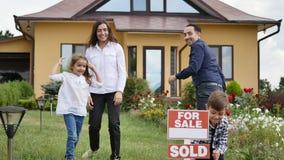 Ευτυχής οικογένεια μπροστά από το καινούργιο σπίτι τους απόθεμα βίντεο