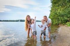 Ευτυχής οικογένεια - πατέρας, μητέρα, δύο γιοι στην παραλία με τα πόδια τους στο νερό στο ηλιοβασίλεμα Στοκ Εικόνα