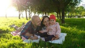Ευτυχής οικογένεια που έχει ένα υπόλοιπο και που φιλά στη φύση με το παιδί στο ηλιοβασίλεμα στο πάρκο Ο πατέρας φιλά τη μητέρα στοκ φωτογραφίες