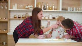Ευτυχής οικογένεια που έχει τη διασκέδαση με το αλεύρι στην κουζίνα απόθεμα βίντεο