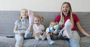 Ευτυχής οικογένεια που έχει τη διασκέδαση στον καναπέ στο σπίτι φιλμ μικρού μήκους