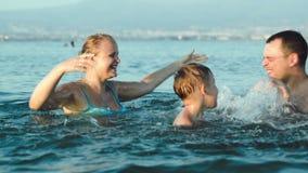 Ευτυχής οικογένεια που έχει τη διασκέδαση στο θαλάσσιο νερό φιλμ μικρού μήκους