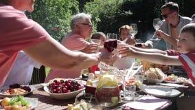 Ευτυχής οικογένεια που έχει το κόμμα κήπων γευμάτων ή καλοκαιριού φιλμ μικρού μήκους