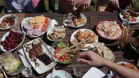 Ευτυχής οικογένεια που έχει το κόμμα κήπων γευμάτων ή καλοκαιριού απόθεμα βίντεο