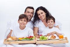 Ευτυχής οικογένεια που έχει το πρόγευμα στο κρεβάτι στοκ εικόνα
