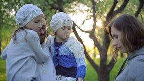 Ευτυχής οικογένεια που αγκαλιάζει σε ένα ανθίζοντας πάρκο φιλμ μικρού μήκους