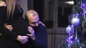 Ευτυχής οικογένεια που αναμένει το μωρό παιδιών, που διακοσμεί το χριστουγεννιάτικο δέντρο απόθεμα βίντεο