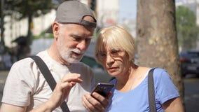 Ευτυχής οικογένεια που απολαμβάνει τις διακοπές Ανώτερο ζεύγος που στέκεται στην οδό που κοιτάζει βιαστικά στο smartphone φιλμ μικρού μήκους