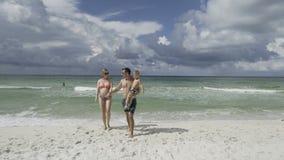 Ευτυχής οικογένεια που απολαμβάνει τον περίπατο πρωινού στην παραλία 4k απόθεμα βίντεο
