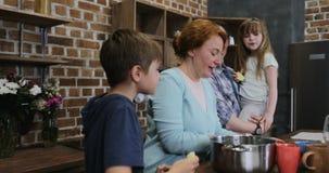 Ευτυχής οικογένεια που βοηθά τη μητέρα με να μαγειρεψει μαζί στην κουζίνα, γονείς με το μικρούς γιο και την κόρη που προετοιμάζου απόθεμα βίντεο