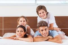 Ευτυχής οικογένεια που βρίσκεται σε ένα κρεβάτι στοκ εικόνες