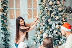 Ευτυχής οικογένεια που διακοσμεί ένα χριστουγεννιάτικο δέντρο με τα boubles στο καθιστικό στοκ φωτογραφία με δικαίωμα ελεύθερης χρήσης