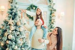 Ευτυχής οικογένεια που διακοσμεί ένα χριστουγεννιάτικο δέντρο με τα boubles στο καθιστικό στοκ εικόνες