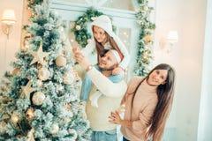 Ευτυχής οικογένεια που διακοσμεί ένα χριστουγεννιάτικο δέντρο με τα boubles στο καθιστικό στοκ φωτογραφίες