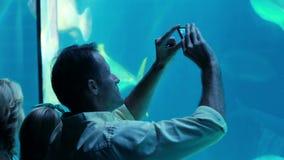 Ευτυχής οικογένεια που εξετάζει τη δεξαμενή ψαριών απόθεμα βίντεο
