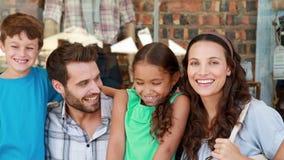 Ευτυχής οικογένεια που εξετάζει τη κάμερα στη λεωφόρο αγορών απόθεμα βίντεο
