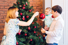 Ευτυχής οικογένεια που διακοσμεί το χριστουγεννιάτικο δέντρο από κοινού Πατέρας, μητέρα και γιος παιδί χαριτωμένο κατσίκι Στοκ φωτογραφία με δικαίωμα ελεύθερης χρήσης