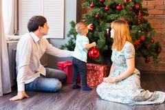 Ευτυχής οικογένεια που διακοσμεί το χριστουγεννιάτικο δέντρο από κοινού Πατέρας, μητέρα και γιος παιδί χαριτωμένο κατσίκι Στοκ Εικόνες