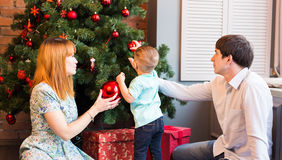 Ευτυχής οικογένεια που διακοσμεί το χριστουγεννιάτικο δέντρο από κοινού Πατέρας, μητέρα και γιος παιδί χαριτωμένο κατσίκι Στοκ Εικόνα