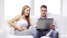 Ευτυχής οικογένεια που κοιτάζει με το φορητό προσωπικό υπολογιστή απόθεμα βίντεο