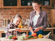 Ευτυχής οικογένεια που μαγειρεύει τα υγιή σπιτικά τρόφιμα στοκ φωτογραφίες