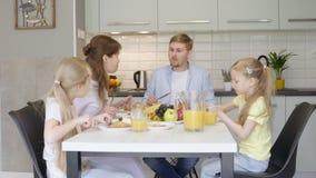 Ευτυχής οικογένεια που μιλά κατά τη διάρκεια του προγεύματος απόθεμα βίντεο
