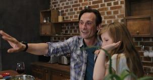 Ευτυχής οικογένεια που μιλά κάνοντας την τηλεοπτική κλήση με το φορητό προσωπικό υπολογιστή από την κουζίνα κατά τη διάρκεια του  απόθεμα βίντεο