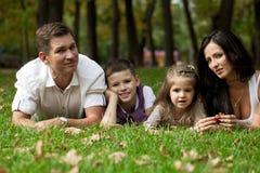 Ευτυχής οικογένεια που ξαπλώνει στον κήπο στοκ φωτογραφία με δικαίωμα ελεύθερης χρήσης