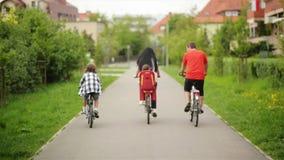 Ευτυχής οικογένεια που οδηγά στα ποδήλατά τους στο πάρκο μια ηλιόλουστη ημέρα Έχουν πολλή διασκέδαση από κοινού απόθεμα βίντεο