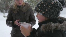 Ευτυχής οικογένεια που πίνει το καυτό τσάι έξω το χειμώνα 96fps φιλμ μικρού μήκους