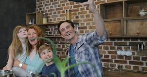 Ευτυχής οικογένεια που παίρνει τη φωτογραφία Selfie μαγειρεύοντας στους γονείς και τα παιδιά κουζινών που προετοιμάζουν στο σπίτι απόθεμα βίντεο