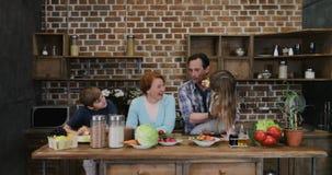 Ευτυχής οικογένεια που περιμένει την προετοιμασία των τροφίμων στους εύθυμους γονείς και τα παιδιά κουζινών που χτυπούν τα χέρια  φιλμ μικρού μήκους