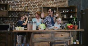 Ευτυχής οικογένεια που περιμένει την προετοιμασία των τροφίμων στους εύθυμους γονείς και τα παιδιά κουζινών που δίνουν υψηλά πέντ φιλμ μικρού μήκους