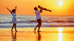 Ευτυχής οικογένεια που περπατά με τη διασκέδαση στην παραλία θάλασσας ηλιοβασιλέματος Στοκ Εικόνες